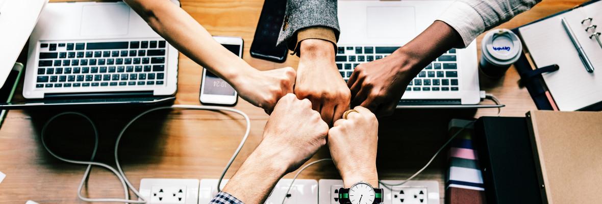 kädet yhdessä kokouspöydällä